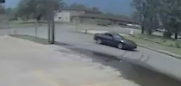 Dark colored 2-door vehicle driving down the street from street camera