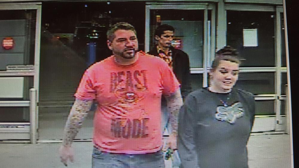 security camera image of man and woman leaving store - man wearing a red shirt that says Beast Mode and woman's shirt has Fox logo