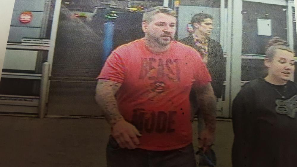 security camera image of a man and a woman leaving a store, the man wearing red Beast Mode shirt and woman wearing black Fox long-sleeved shirt