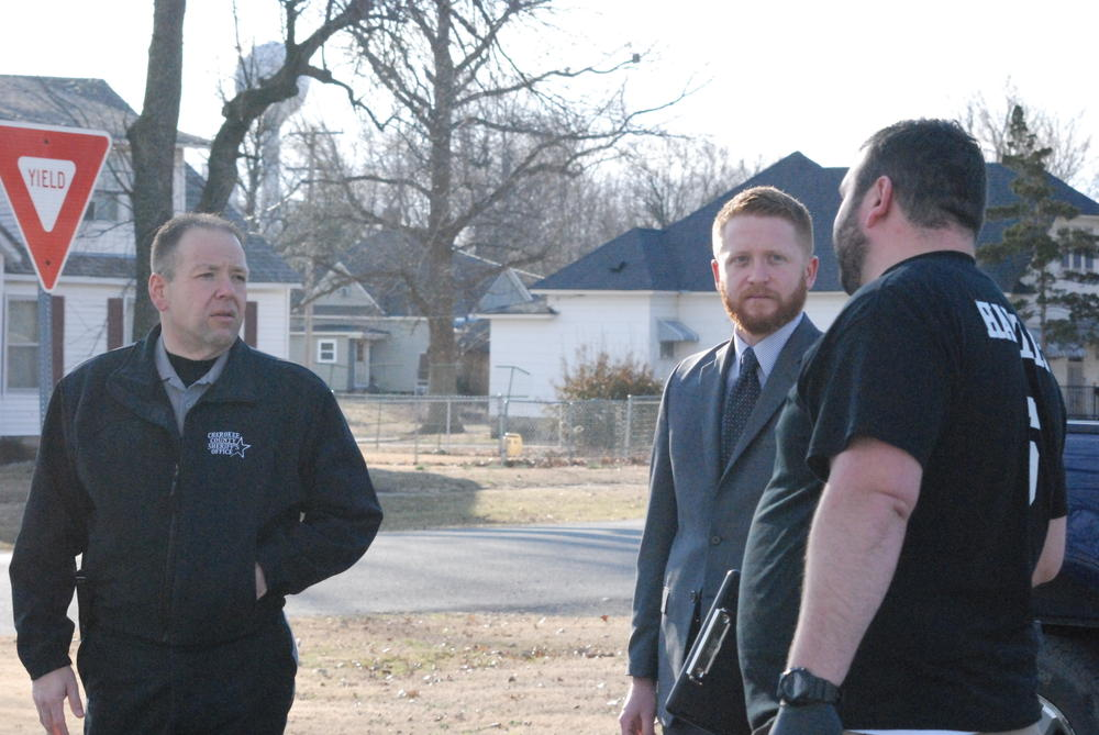Sheriff David Groves and County Attorney Jake Conard get briefed from Sgt. Investigator Beau Hamlin