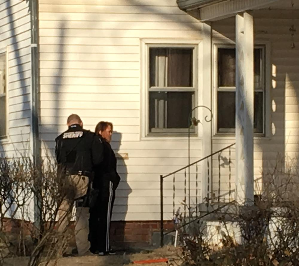 Officer and woman standing outside residence