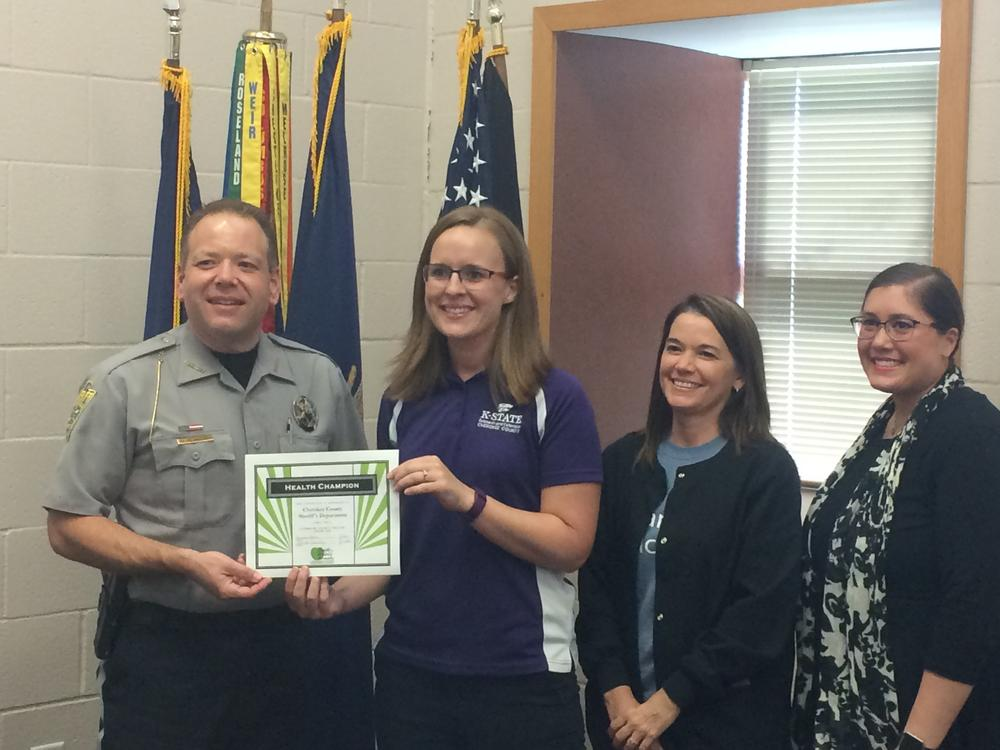 Sheriff David Groves, Christina Holmes, Teresa Cassidy and Tiffany Green standing and smiling with award